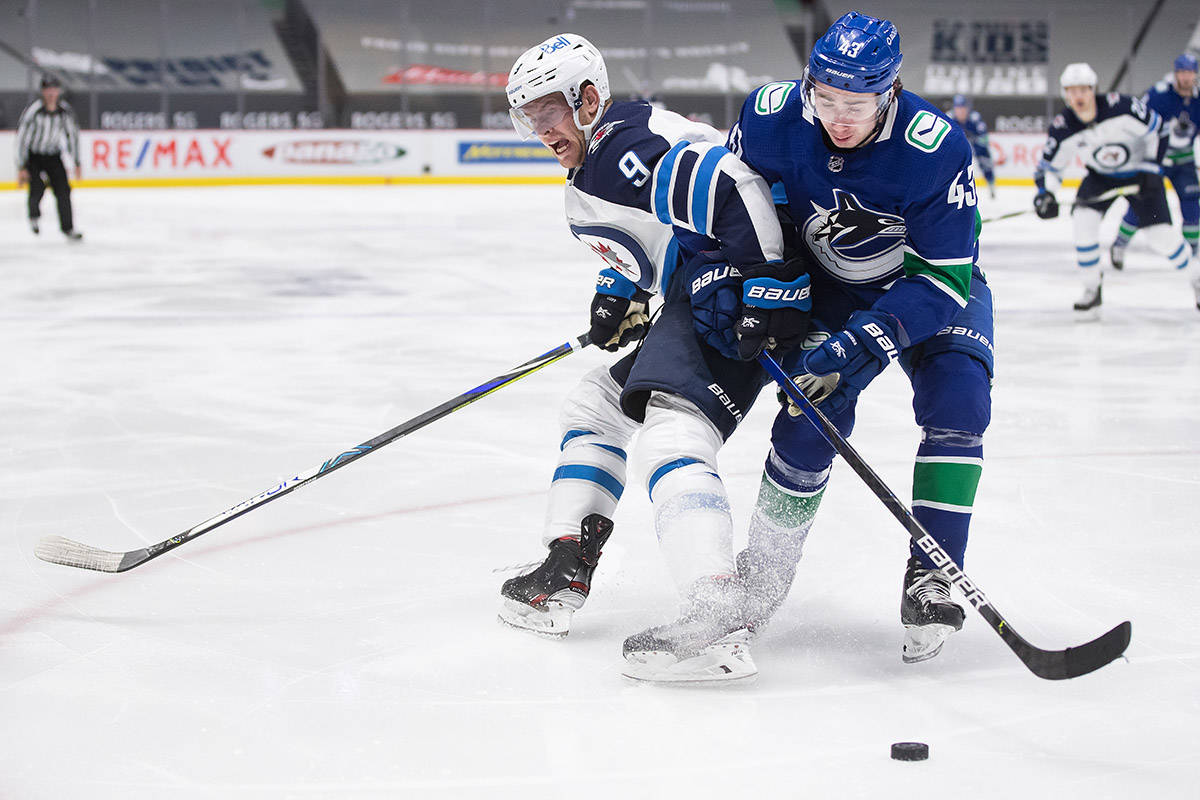 Winnipeg Jets' Andrew Copp (9) and Vancouver Canucks' Quinn Hughes (43) vie for the puck during the third period of an NHL hockey game in Vancouver, on Wednesday, March 24, 2021. THE CANADIAN PRESS/Darryl Dyck